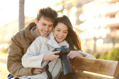 stock-photo-76402023-couple-of-tourists-reviewing-photos-in-a-dslr-camera